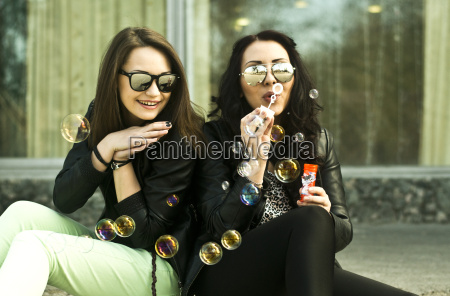 two young woman having fun blowing