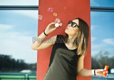 young woman having fun blowing bubbles