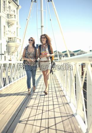 young women walking along pier cape