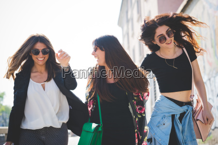 three young female friends strolling and