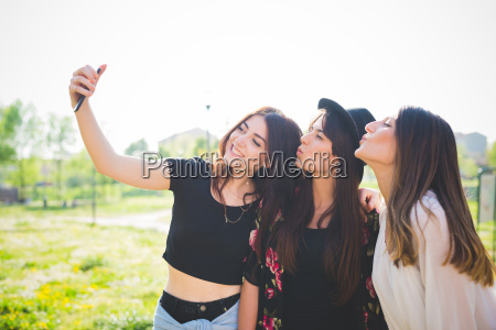 three young female friends puckering lips
