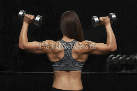 young woman lifting weights rear view