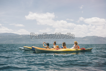 four young female friends kayaking on