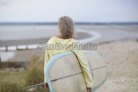 senior woman walking towards beach carrying