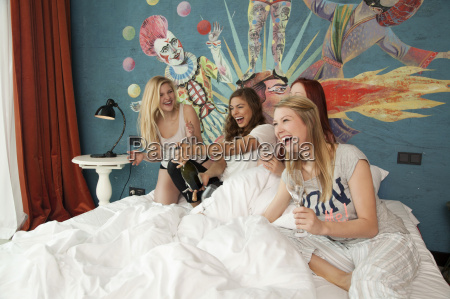 four young women friends uncorking champagne