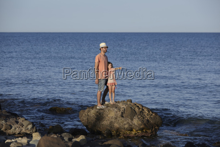 father and daughter standing on rock