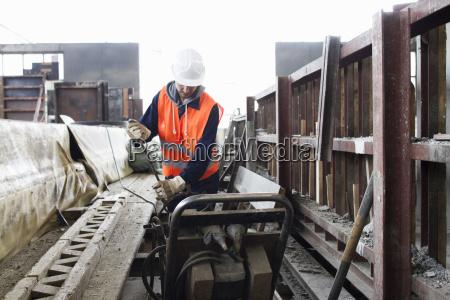 fabrikarbeiter waehlt stahlstange in betonbewehrungsfabrik
