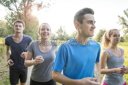 group of friends running through field
