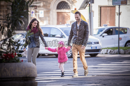 couple and daughter holding hands on