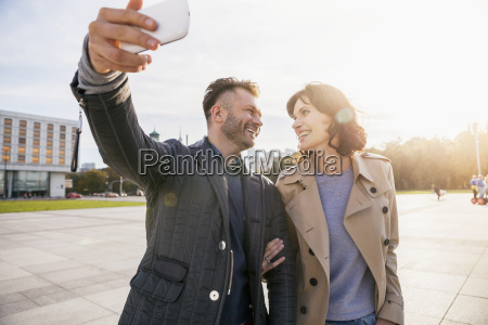 mid adult couple taking selfie on