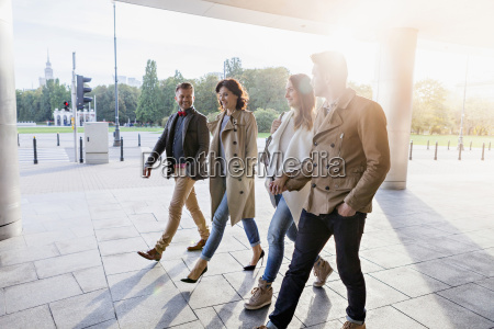 four mid adult friends walking together