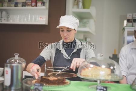 barista serving chocolate cake at cafe