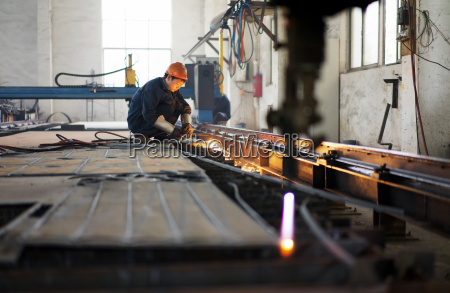 worker using equipment in crane manufacturing