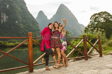 three adult female friends taking smartphone