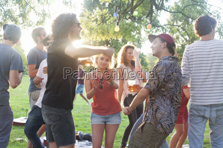 adult friends dancing at park party