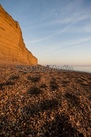 shingle beach and cliffs at dusk