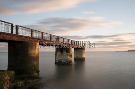 rusting pier at dusk overcombe beach