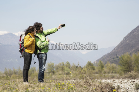 hiking couple taking smartphone selfie vogogna