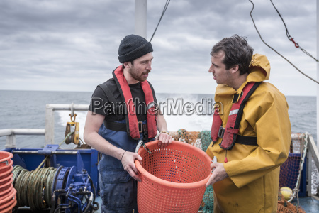 research scientists and fisherman inspecting catch