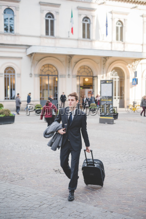 young businessman commuter walking along cobbled