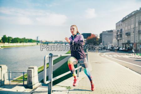 mid adult female runner running along