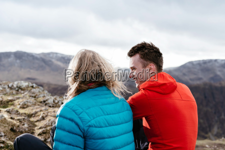 young couple sitting on hilltop rear