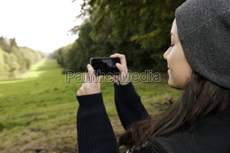 young woman photographing field on smartphone