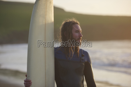 young male surfer at beach devon