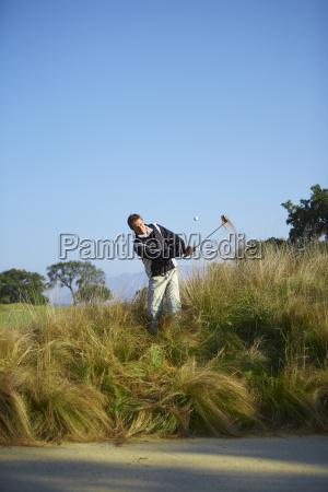 golfer taking golf swing in tall