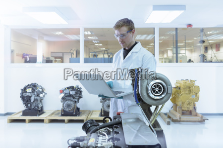 scientist using laptop in turbo charger