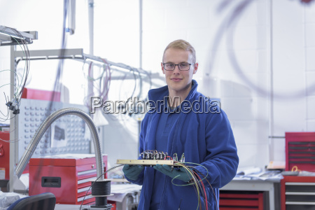 portrait of apprentice electronics worker in