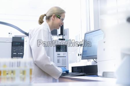 female scientist at workstation testing oil