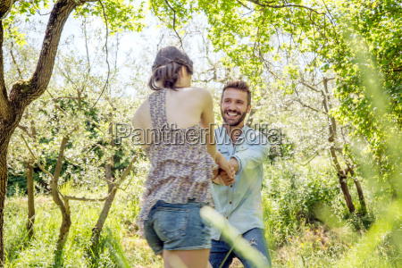 young couple holding hands in forest
