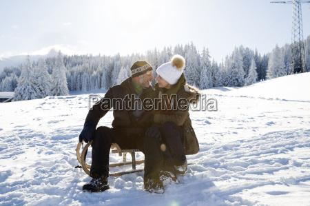 senior couple on snowy landscape sitting