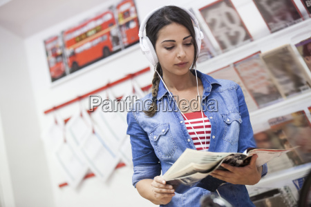 young woman wearing headphones looking through