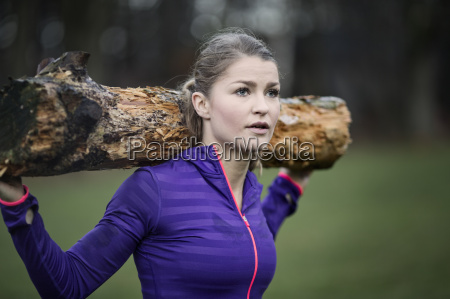 young woman carrying tree branch on