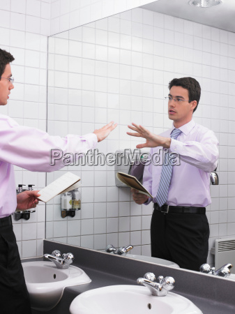man practicing speech in office washroom