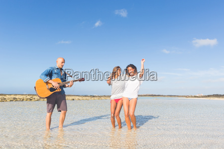 man playing acoustic guitar with two