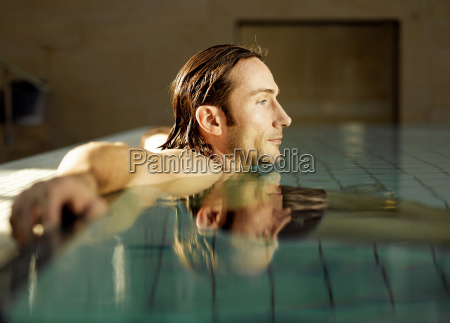 mature man sitting in swimming pool