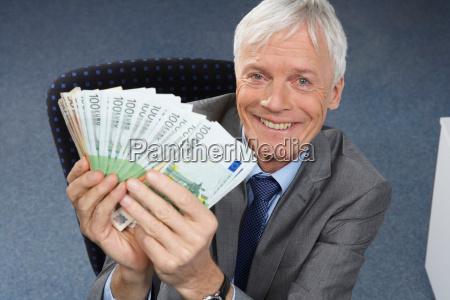 businessman holding money smiling