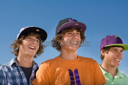teen boys wear baseball hat smiling