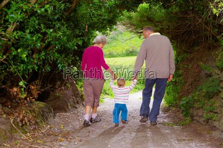 senior couple walking with child