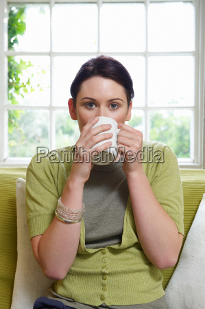 young woman on couch with mug