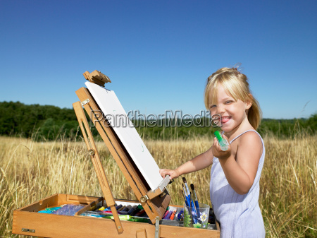 girl painting in a field smiling