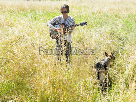 man playing guitar in a field