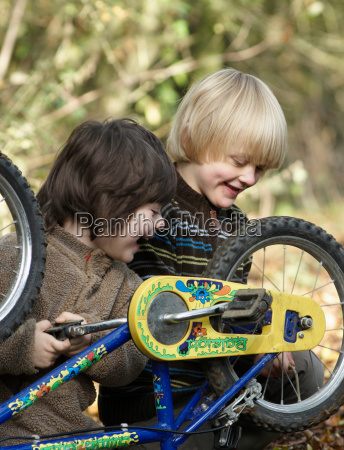 two boys examine bikes on country