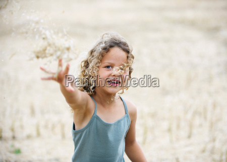 young girl throwing wheat in field
