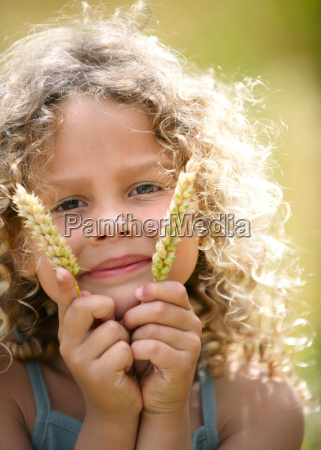 young girl holds up ears of