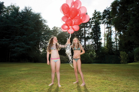 two girls with red balloons