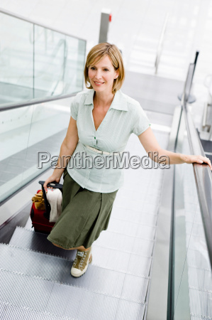 woman walking an escalator